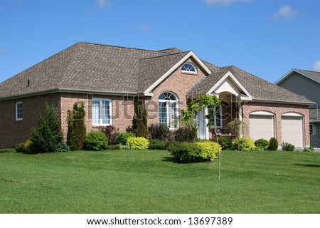 A newly constructed brick family home with garages. - stock photo