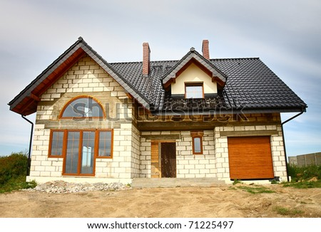 A newly constructed house with lots of roof detailing.