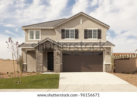 A Newly Constructed Modern Home Facade and Yard. - stock photo