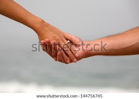 A Newly Engaged couple hold hands showing her Engagement Ring  on the beach with the Pacific Coast Ocean out of focus in the background. Represents Marriage, Romance, Engagement, Love, and Commitment