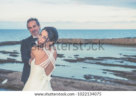 A newly married couple is embracing. On the background, sea and rocks of the wonderful location of Plemmirio natural park in Siracusa (Sicily), .