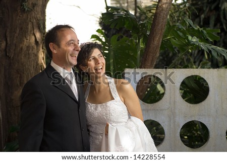 A newly married couple smile away from the camera, while still in their wedding clothes. A scenic area fills the background. - horizontally framed - stock photo
