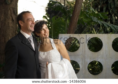 A newly married couple smile, while still in their wedding clothes. A scenic area fills the background. - horizontally framed - stock photo