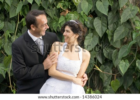 A newly married couple stare at each other, while in their wedding clothes. - horizontally framed - stock photo