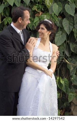 A newly married couple stare at each other, while in their wedding clothes. - vertically framed - stock photo
