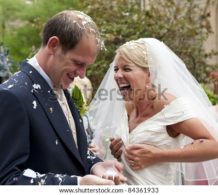 A newly wed Bride and Groom covered in confetti - stock photo