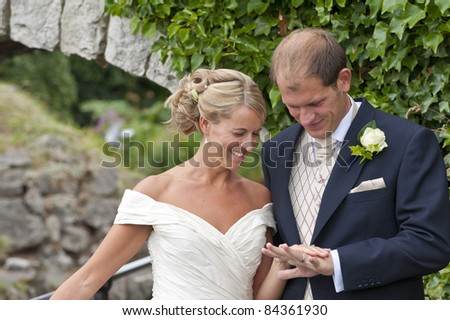 A newly wed Bride and Groom looking at their wedding rings - stock photo