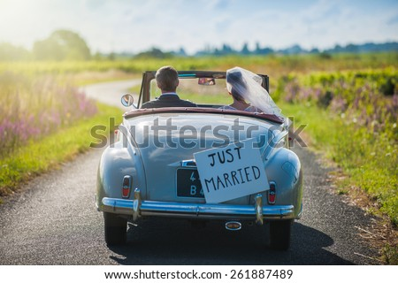 A newlywed couple is driving a convertible retro car on a country road for their honeymoon, rear view - stock photo