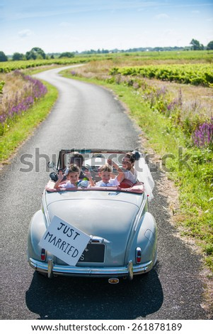 A newlywed couple is driving a retro car on a country road with their two beautiful children, they are looking at camera - stock photo
