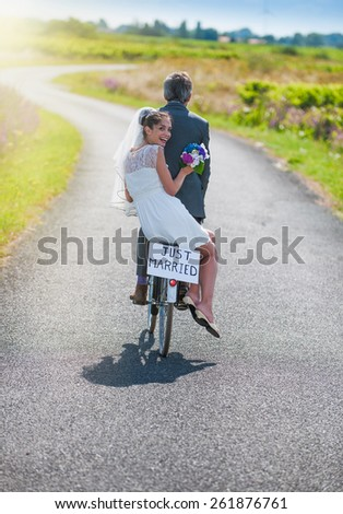 A newlywed couple is taking the road on a bike. They are having fun for their honeymoon - stock photo