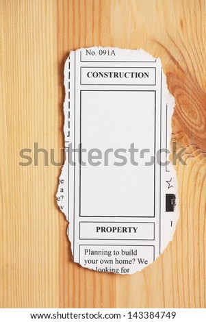A newspaper clipping from the classified ads section with a banner for construction and property alongside copy space on a wood or timber background.