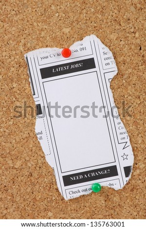 A newspaper clipping with copy space advertising the latest jobs and pinned to a cork notice board - stock photo