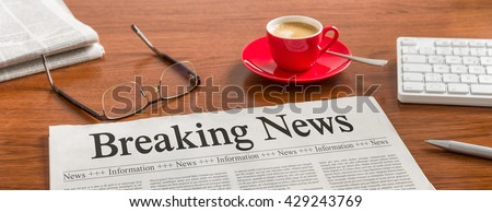 A newspaper on a wooden desk - Breaking News - stock photo