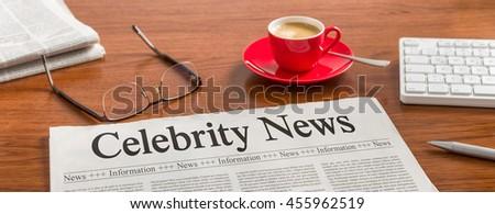 A newspaper on a wooden desk - Celebrity News - stock photo