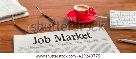 A newspaper on a wooden desk - Job Market - stock photo