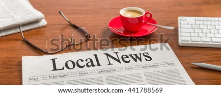 A newspaper on a wooden desk - Local News - stock photo
