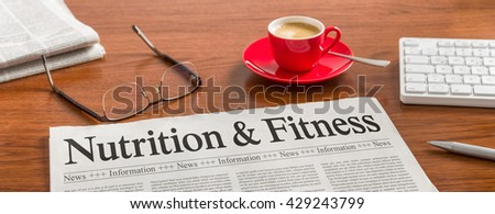 A newspaper on a wooden desk - Nutrition and Fitness - stock photo