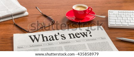 A newspaper on a wooden desk - Whats new - stock photo