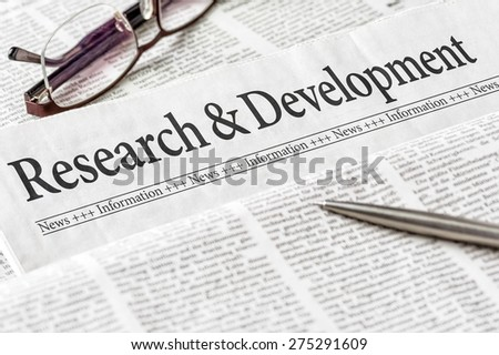 A newspaper with the headline Research and Development - stock photo