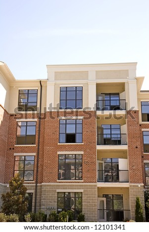 A nice brick and stucco apartment building against blue sky - stock photo