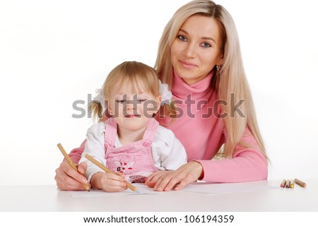 A nice Caucasian mama with her daughter paint crayons on a white background