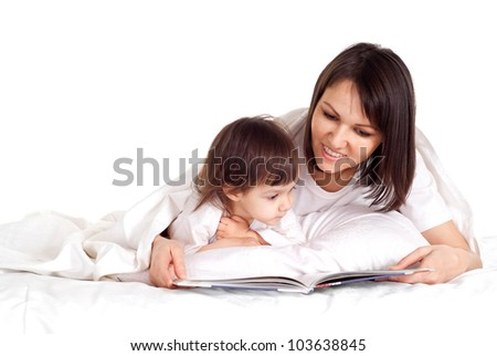 A nice Caucasian mother with her daughter lying on the bed with a book