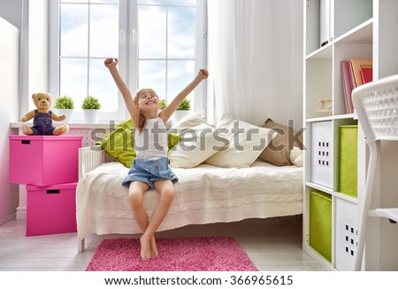 A nice child girl enjoys sunny morning. Good morning at home. Child girl wakes up from sleep. - stock photo