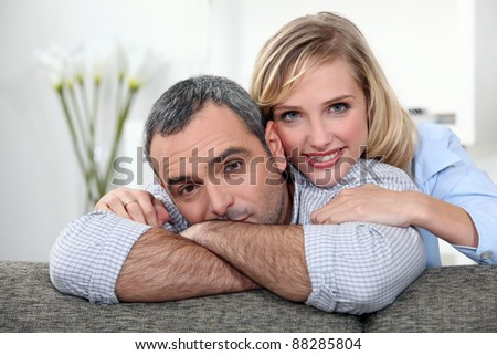 A nice couple cuddling on a couch. - stock photo