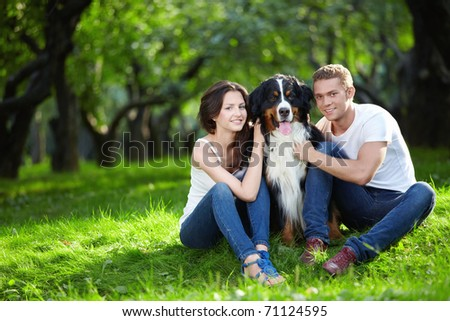 A nice couple with a dog in the park - stock photo