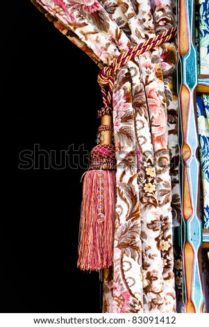 A nice curtain tied back with dark copyspace - stock photo