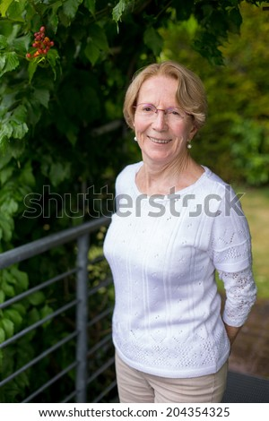 A nice elderly woman is smiling at the camera in a beautiful garden