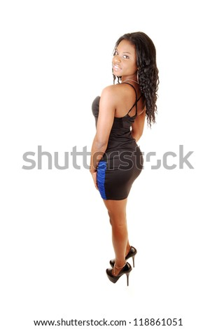 A nice figured young black woman standing for white background in the  studio in a black and blue dress, with her long black hair.