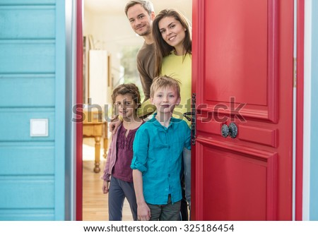 A nice four people family is opening their stylish red door to welcome the guest. The parents and their two children are smiling and wearing casual clothes. The house have blue wall and wooden floors