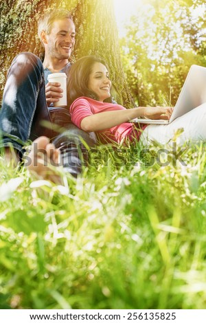 A nice grey hair man and a woman are sitting in the grass, looking at their computer. The man is sitting against a tree holding a coffee while his girlfriend is laying against him.  - stock photo