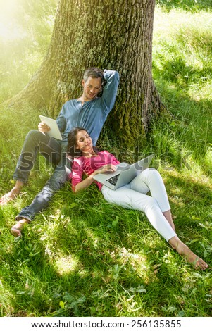 A nice grey hair man and a woman are sitting in the grass, looking at their tablet and computer. The man is sitting against a tree while his girlfriend is laying against him.  - stock photo