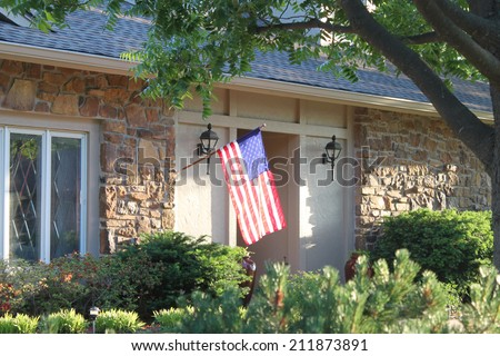 A nice house with a large American flag - stock photo