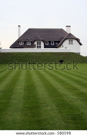 A nice house with green grass in front of it. (Ideal copyspace) - stock photo