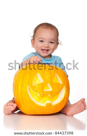 A nice image of a Hispanic baby holding a pumpkin.