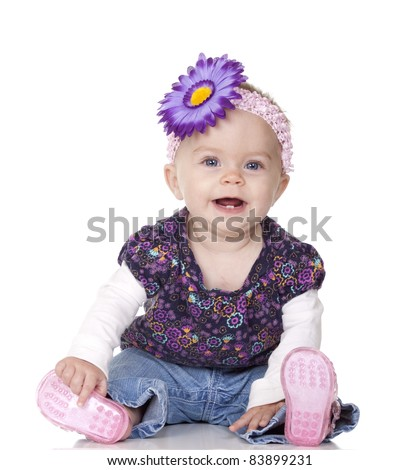 A nice image of an 8 month old baby isolated with reflection on white.  The cute baby girl has a purple bow in her hair. - stock photo