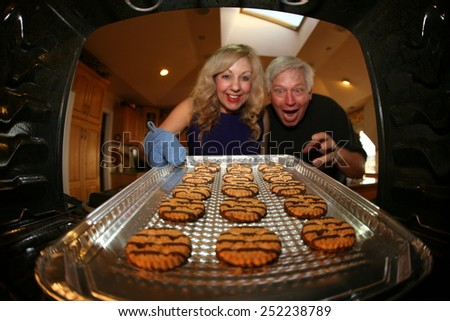 A nice lady bakes Cookies for her favorite pool man as a special Thank You. Shot from inside the oven out for a unique view. Focus on the cookie with the people slightly out of focus. - stock photo