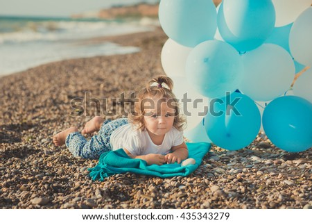 A nice little girl lying on the beach with blue  air balloons. Portrait of a little girl with blue balls on the beach. - stock photo
