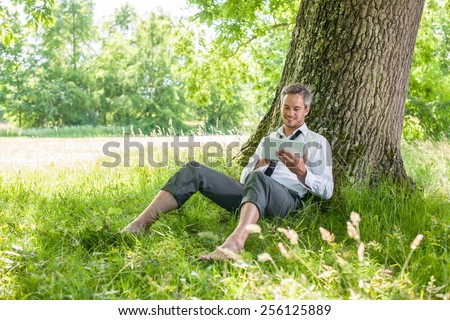 A nice looking grey hair man is sitting against a tree in the grass, looking at his tablet. He is relaxing, enjoying the shadow of the tree in a sunny day. - stock photo