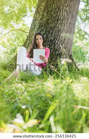 A nice looking woman is sitting against a tree in the grass, looking at her tablet. She is relaxing, enjoying the shadow of the tree in a sunny day.