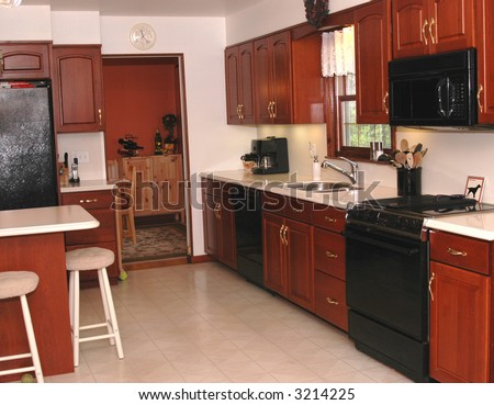 A nice modern kitchen with cherry cabinetry - stock photo