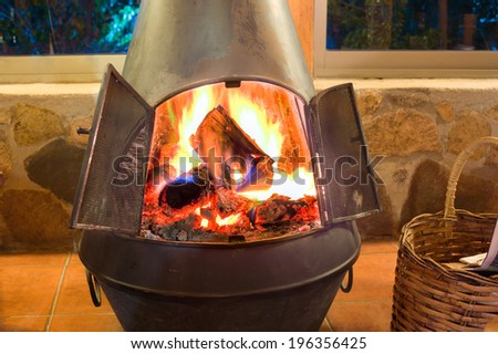 A nice oven in a cozy living room with a crackling fire inside - stock photo