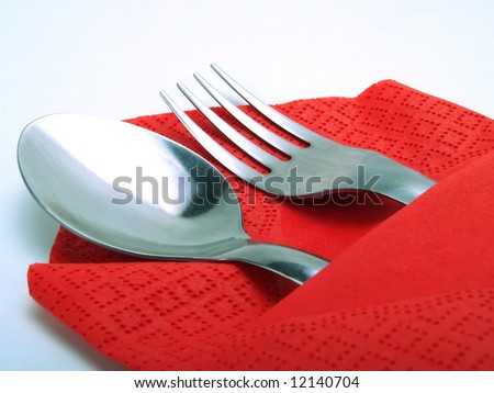 A nice place with a silvery spoon and fork, covered by a nice red napkin - stock photo