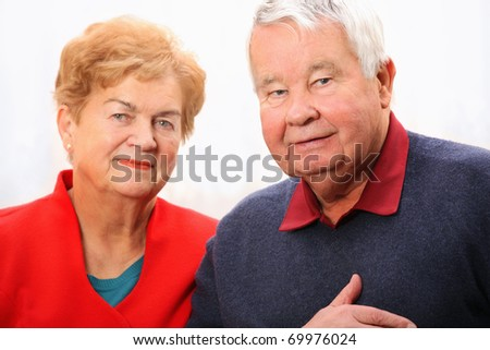A nice portrait of a senior couple standing against white background - stock photo