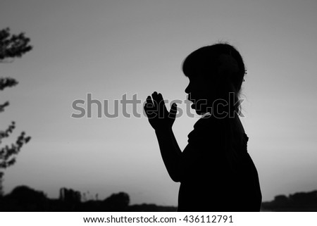 a nice silhouette of a little girl praying - stock photo