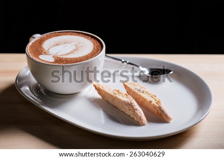 A nice view of capuccino and Italian pastries biscotti on black background - stock photo