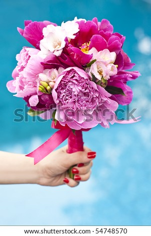A nice wedding bouquet of purple, pink and white peonies held by a bride. - stock photo